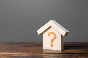 Wooden house with question mark on