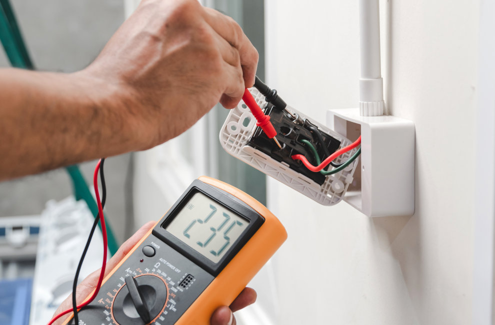 Electrician is using a digital meter to measure the voltage at the power outlet
